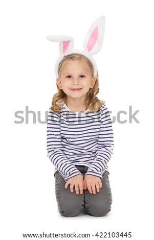Lovely child. Shot of a beautiful little girl wearing bunny ears sitting at the studio looking to the camera smiling isolated on white. - stock photo