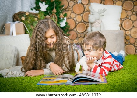 Lovely children - brother and sister reading a book. Boy and girl reading a book lying on the green carpet.