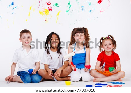 Lovely children with paintbrushes and paint roller - stock photo