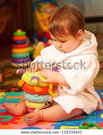 Lovely chubby baby in white bathrobe after bath playing with toys on the floor.