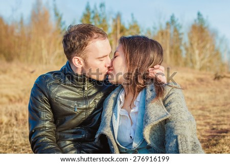 lovely couple boy and girl sitting on the meadow hugging, kissing and enjoying each other in nature
