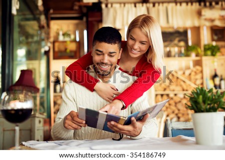 Lovely couple choosing some specialty from menu. While he is sitting she is leaning over his back pointing finger at menu. Shallow depth of field, selective focus on his face. - stock photo
