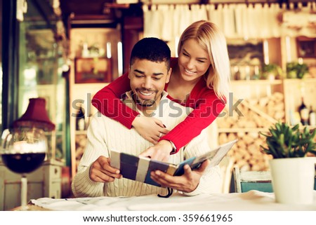 Lovely couple choosing some specialty from menu. While he is sitting she is leaning over his back pointing finger at menu. Shallow depth of field. - stock photo