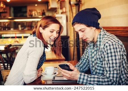 Lovely Couple Enjoying In Cafe Using Technology - stock photo