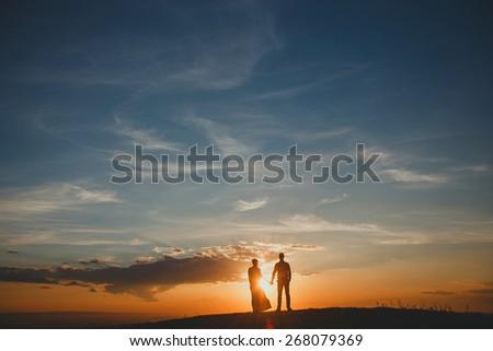 Lovely couple enjoying the sunset - stock photo