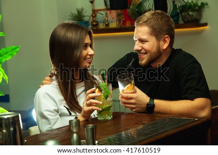 Lovely couple flirting in the bar with alcoholic cocktails and smiling - stock photo
