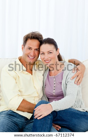 Lovely couple hugging sitting on the sofa of their living room