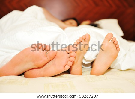 Lovely couple in bed, focus on feet - stock photo