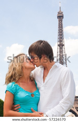 Lovely couple in Paris with Eiffel tower in background - stock photo