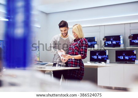 Lovely couple is at store and they are looking for a new tablet. Shallow depth of field. - stock photo
