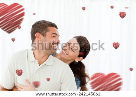 Lovely couple laughing together in the living room against hearts - stock photo