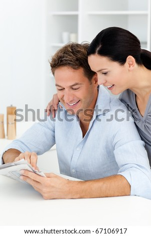 Lovely couple looking at something on the newspaper in the kitchen - stock photo