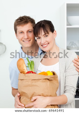 Lovely couple looking at the camera with their shopping bags at home - stock photo