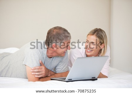 Lovely couple looking at their laptop at home - stock photo