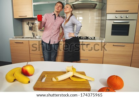 Lovely couple on kitchen with fruits on the table (Focus on table) - stock photo