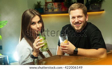 Lovely couple relaxing at the bar with cocktails. Couple looking at the camera and smiling - stock photo
