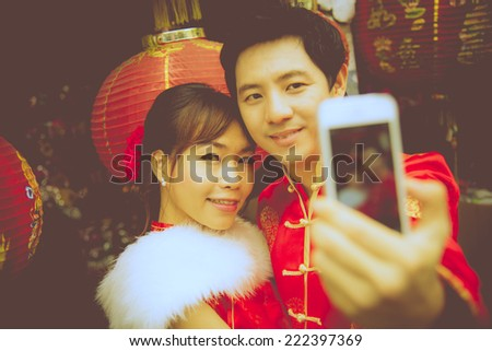 Lovely couple selfie photo by smartphone with red paper chinese lantern in Chinese suit