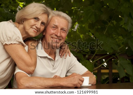 Lovely couple sitting at a table at home on the veranda - stock photo