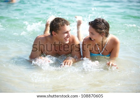 Lovely couple splashing in water enjoying resort life