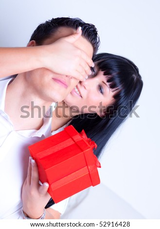 Lovely couple surprising with red gift box - stock photo