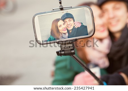 Lovely Couple Taking Selfie Using Smart Phone And Monopod - stock photo