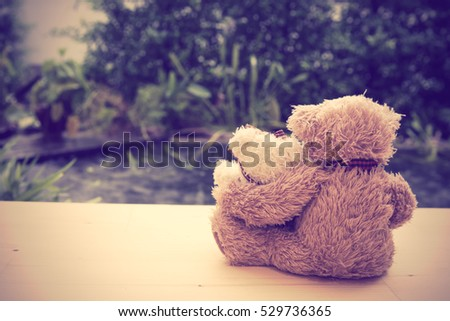 Lovely couple teddy bears sit back  on wooden floor with pool background,retro filter effect