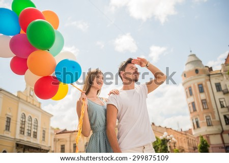Lovely couple walking along the street with balloons and looking away.