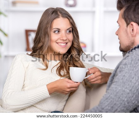 Lovely couple watching TV while drinking tea in their living room - stock photo