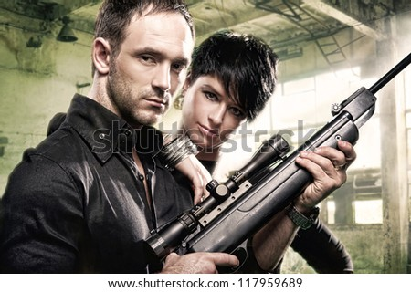 Lovely couple with gun in factory
