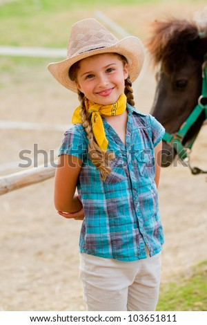 Lovely cowgirl and pony on a ranch - stock photo