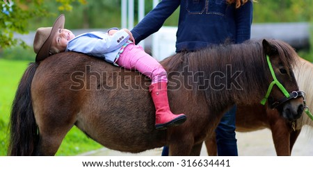Lovely cowgirl lying on the back of little pony horse in the farm. Pretty preschooler girl wearing cowboy hat playing with animals outdoors on sunny day. - stock photo