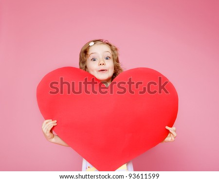 Lovely curly little girl holding large paper heart, over pink background - stock photo