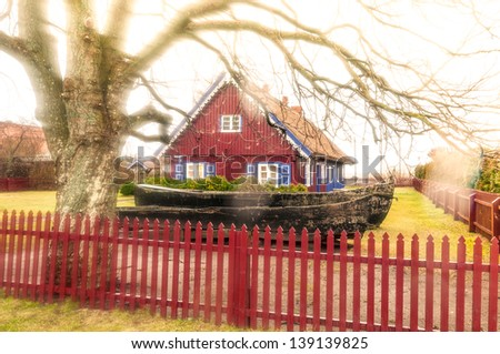 Lovely dark red country house with shutter windows and big yard paled with wooden fence. Large bare tree with long branches and fence in foreground. Quiet rural place. Traditional russian house. - stock photo