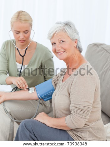 Lovely doctor taking the blood pressure of her patient - stock photo