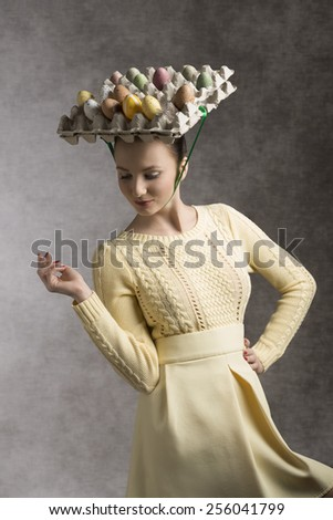 lovely easter portrait of beautiful brunette woman with yellow clothes and funny eggs box on the head - stock photo
