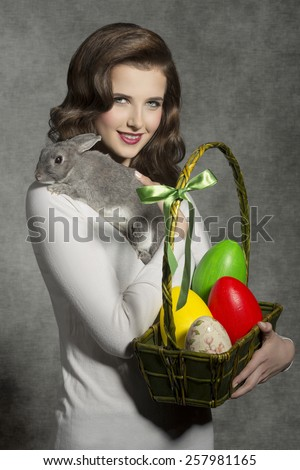 lovely easter portrait of pretty woman with vintage hair-style taking basket with colorful eggs and tender rabbit on her shoulder  - stock photo