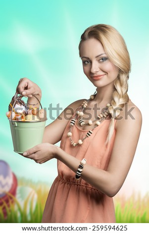 lovely easter portrait of sensual blonde girl with spring style and small bucket with colorful decorated eggs  - stock photo