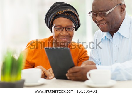 lovely elderly african couple using tablet computer at home - stock photo