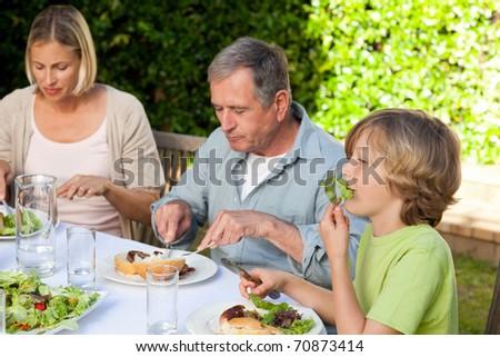Lovely family eating in the garden - stock photo