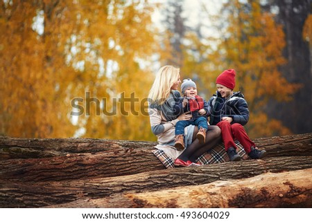 Lovely family in the autumn on the nature. Mother and her sons laugh. Happy people.