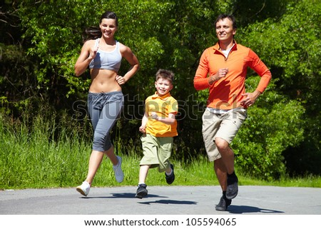 Lovely family jogging in the open air - stock photo
