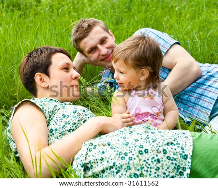 Lovely family lying in the grass - stock photo