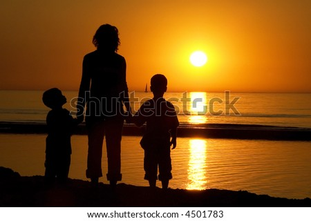 Lovely family picture of a mother and her two sons standing at a beach while looking at a sunset.
