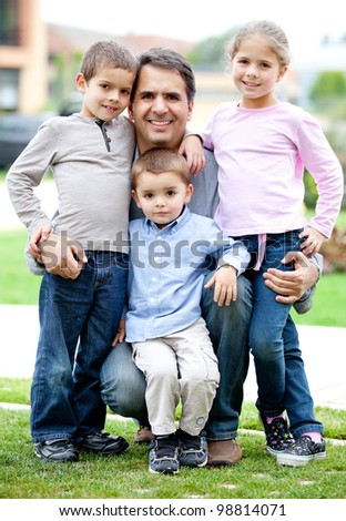 Lovely family portrait of father with his children smiling outdoors - stock photo