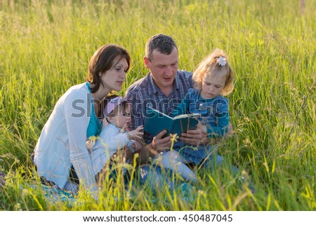 Lovely family reading a book on the grass - stock photo