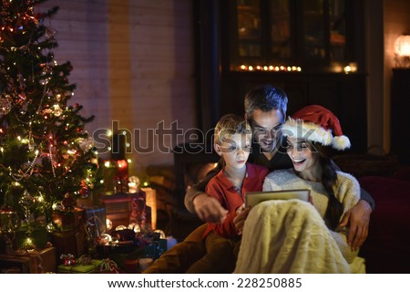 lovely family sharing a digital tablet near the wood stove on a winter evening, enjoying the warmth of Christmas in their living room, the young woman wears a hat of Santa Claus - stock photo