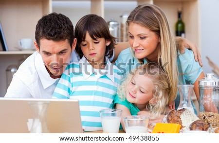 Lovely family using laptop during the breakfast in the kitchen - stock photo