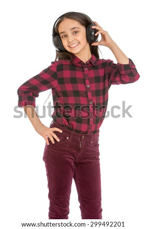 Lovely fashion small girl Oriental appearance with long dark hair. put on the head of large black headphones and listens to music , the girl dressed in a plaid shirt and corduroy jeans, close-up - stock photo
