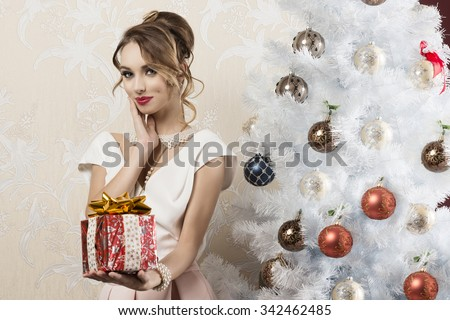 lovely fashion woman with elegant style, pearl necklace, stylish make-up and hair-style posing near christmas tree in indoor shoot with gift box in the hand