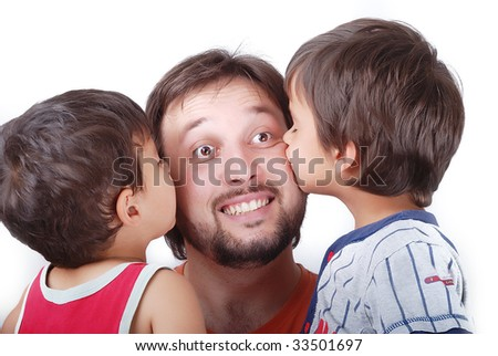 Lovely father is been kissed by his two sons - stock photo